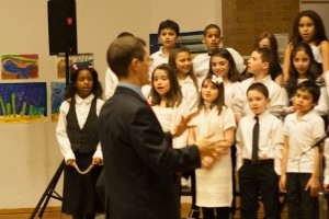 Nick, conducting a choir of 3rd and 4th grade students.